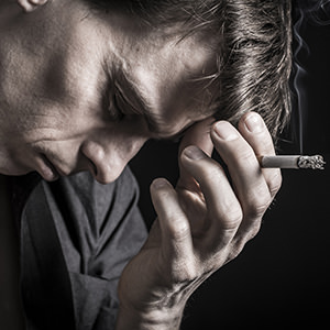 bigstock-Depressed-man-smoking-cigarett-59434430