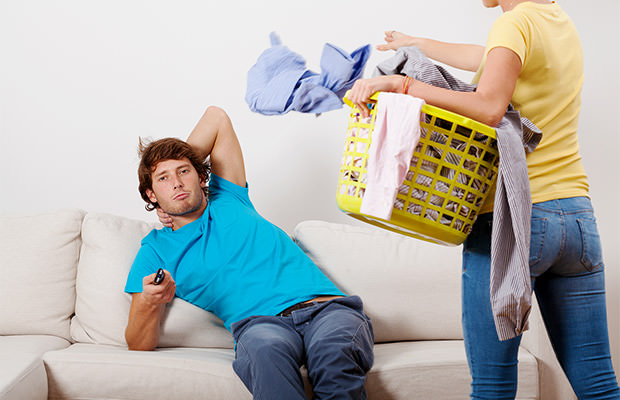 bigstock-Woman-Cleaning-Man-Chilling-59553983