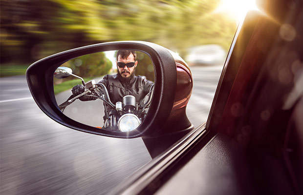 bigstock-Biker-in-rear-view-mirror-76521551
