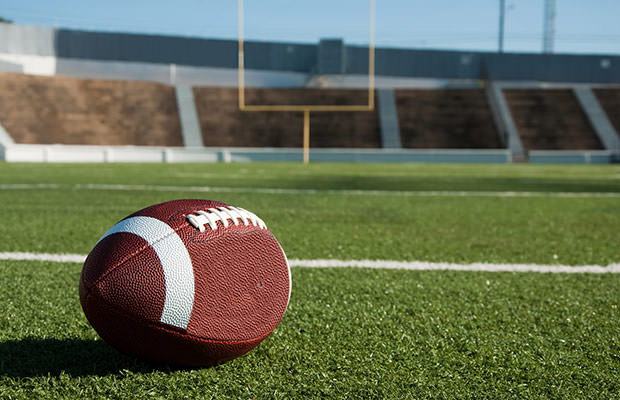 bigstock-American-Football-On-Field-8491306