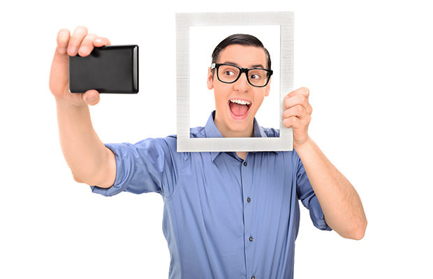 bigstock-Man-taking-a-selfie-and-holdin-62873521