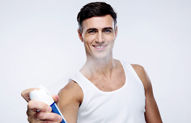 bigstock-Happy-man-spraying-deodorant-o-77792504