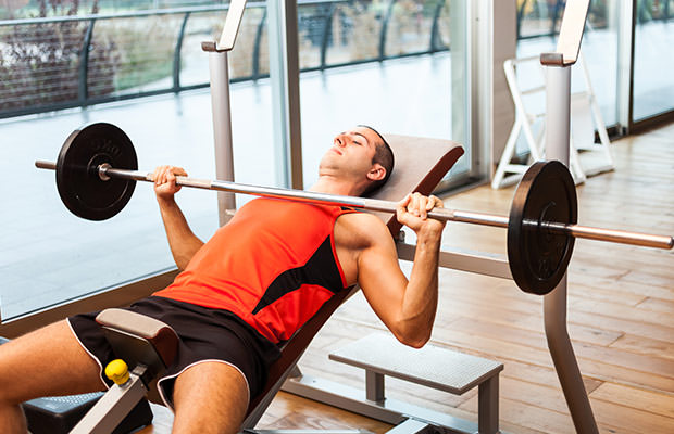 bigstock-Man-lifting-a-weight-in-a-fitn-78437996