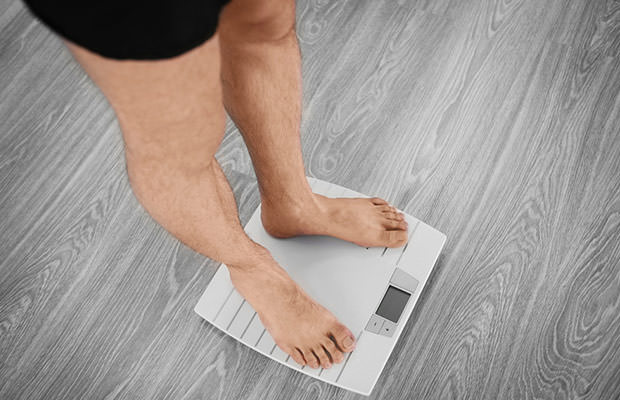 bigstock-Man-standing-on-weight-scale-144563333